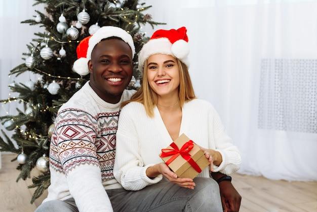 Porträt des lächelnden jungen paares sitzen nahe weihnachtsbaum