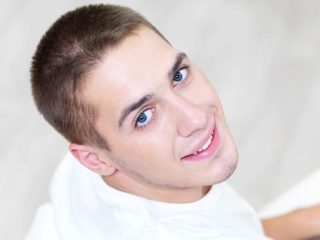 Porträt des lächelnden jungen schönen mannes zu hause - hoher winkel