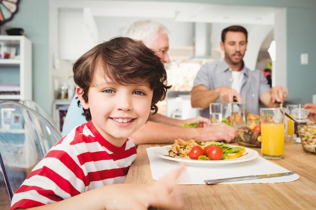 Porträt des lächelnden jungen sitzend an speisetische