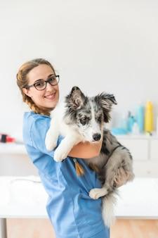 Porträt des lächelnden jungen weiblichen tierarztes, der den hund in der klinik trägt
