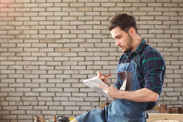 Porträt des lächelnden jungen zimmermanns im inneren der werkstatt mit notizbuch in seinen händen