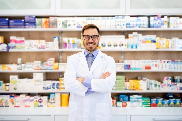 Porträt des lächelnden kaukasischen apothekers, der in drogerie mit verschränkten armen steht.