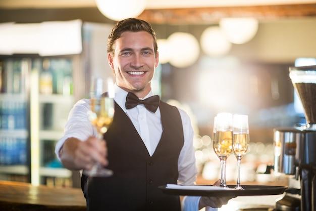 Porträt des lächelnden kellners ein glas champagner anbietend