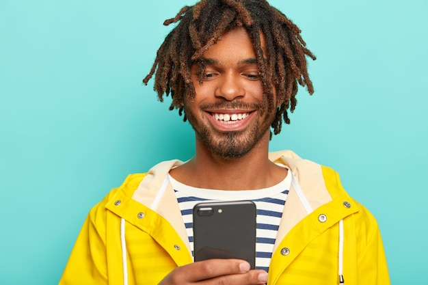 Porträt des lächelnden kerls mit dreadlocks, gekleidet in gelbem regenmantel, verwendet ein mobiltelefon, lokalisiert auf blauem hintergrund