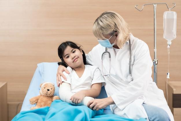 Porträt des lächelnden kinderarztes und des kleinen patienten auf bett