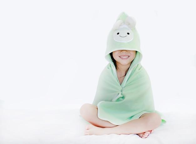 Porträt des lächelnden kindermädchens nach bad bedeckte kopf und augen mit tuch auf weißem backgr