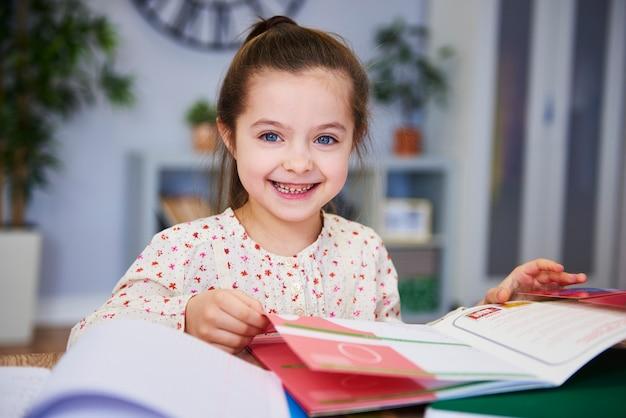 Porträt des lächelnden kindes, das zu hause studiert