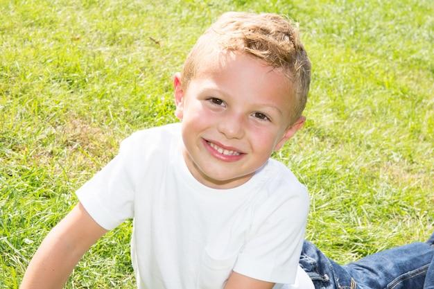 Porträt des lächelnden kindes draußen. junge, der die kamera mit einem hübschen lächeln auf seinem gesicht betrachtet