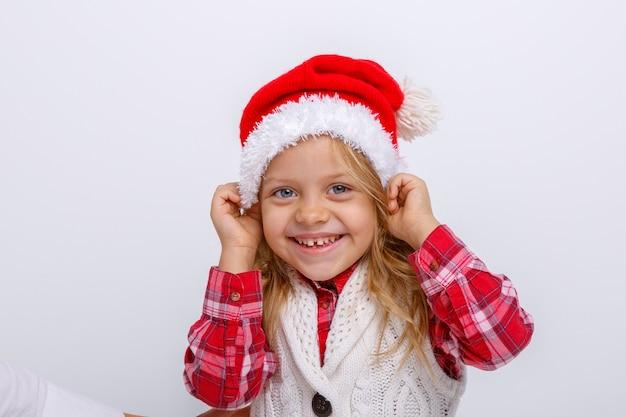 Porträt des lächelnden kleinen blonden mädchens in sankt-hut auf weißen hintergründen