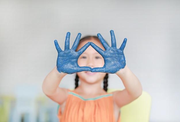Porträt des lächelnden kleinen mädchens, das durch ihre blauen hände gemalt im kinderraum schaut