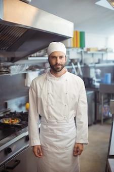 Porträt des lächelnden kochs, der in der kommerziellen küche steht