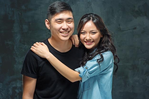 Porträt des lächelnden koreanischen paares auf einem grau