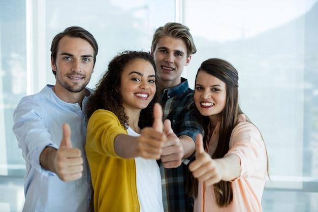 Porträt des lächelnden kreativen geschäftsteams, das daumen oben im büro zeigt