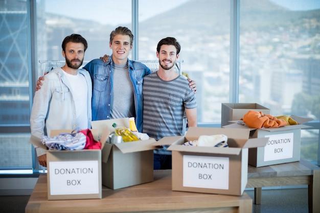Porträt des lächelnden kreativen geschäftsteams, das mit spendenbox im büro steht