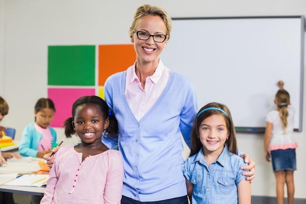 Porträt des lächelnden lehrers und der kinder, die zusammen mit arm herum stehen