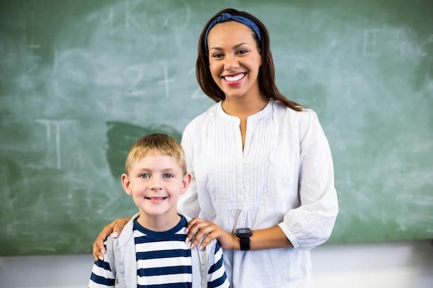 Porträt des lächelnden lehrers und des schülers, die im klassenzimmer stehen