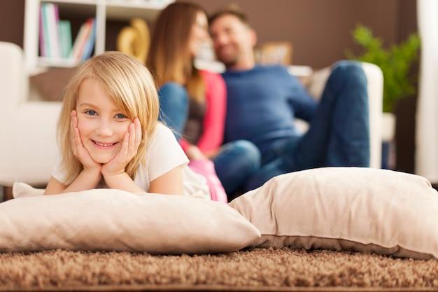 Porträt des lächelnden mädchens, das auf teppich im wohnzimmer entspannt