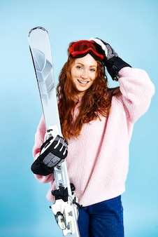 Porträt des lächelnden mädchens, das ihre skier hält