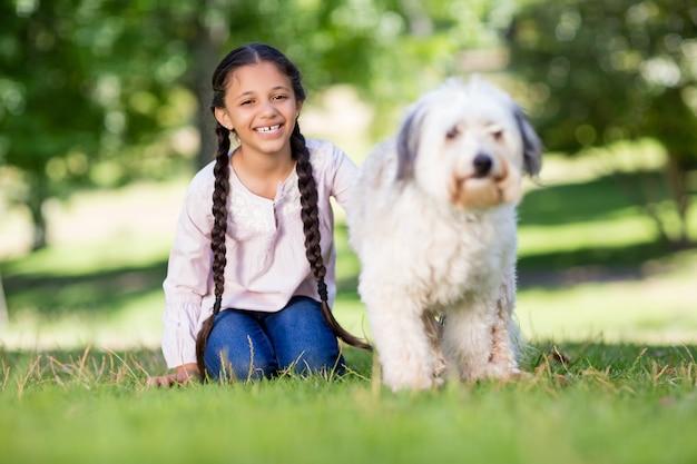 Porträt des lächelnden mädchens, das mit ihrem haustierhund spielt