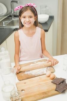 Porträt des lächelnden mädchens, das teig mit holzstift auf küche rollt