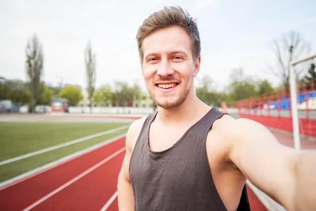 Porträt des lächelnden männlichen athleten, der selfie am handy spricht