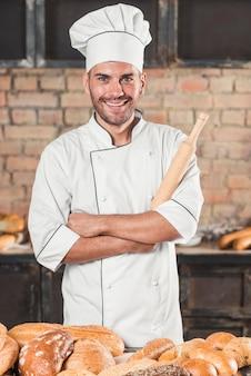 Porträt des lächelnden männlichen bäckers, der hinter den broten auf tabelle steht