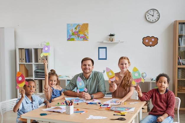 Porträt des lächelnden männlichen lehrers mit multiethnischer gruppe von kindern, die bilder von weltraumraketen zeigen, während kunst- und handwerksunterricht in der vorschule oder im entwicklungszentrum genießen