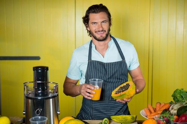 Porträt des lächelnden männlichen personals, das glas saft und papaya hält
