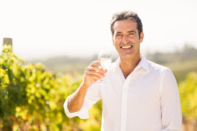 Porträt des lächelnden männlichen winzers, der ein glas wein hält