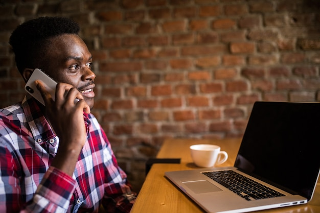 Porträt des lächelnden mannes, der auf handy spricht, während er in einem café mit einem laptop sitzt