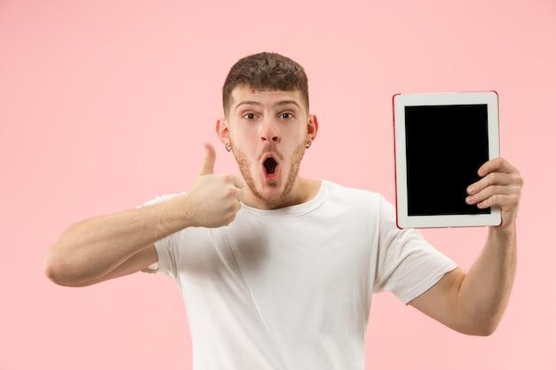 Porträt des lächelnden mannes, der auf laptop mit leerem bildschirm lokalisiert auf weiß zeigt