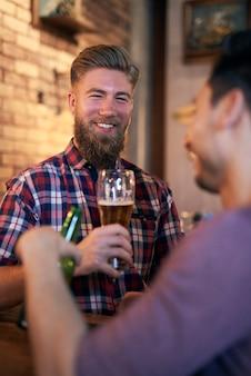 Porträt des lächelnden mannes, der bier in der kneipe trinkt