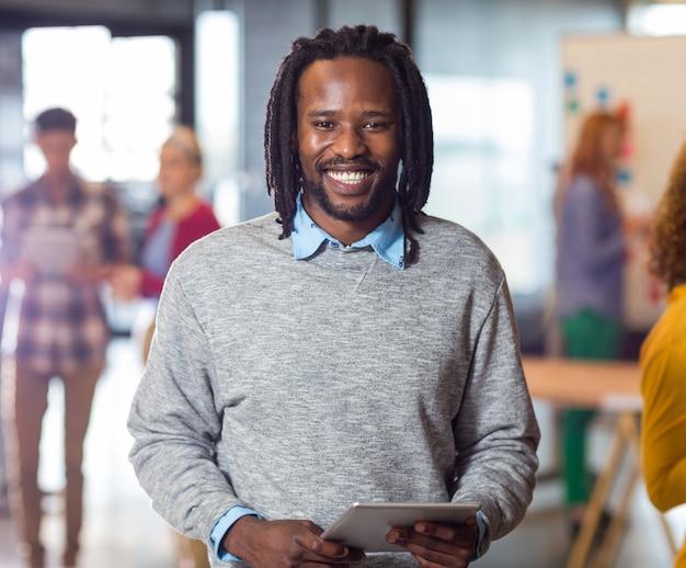 Porträt des lächelnden mannes, der digitales tablett hält