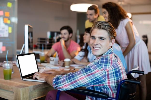 Porträt des lächelnden mannes, der laptop benutzt, während er mit seinem team im büro arbeitet