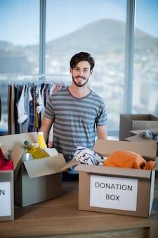 Porträt des lächelnden mannes, der mit spendenbox im büro steht