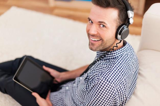 Porträt des lächelnden mannes, der musik zu hause hört