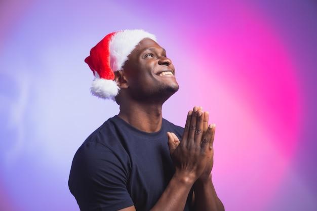 Porträt des lächelnden mannes des positiven afroamerikaners in sankt-hut und beiläufigem t-shirt auf buntem hintergrund, weihnachtszeit. winterferien und emotionales menschenkonzept.