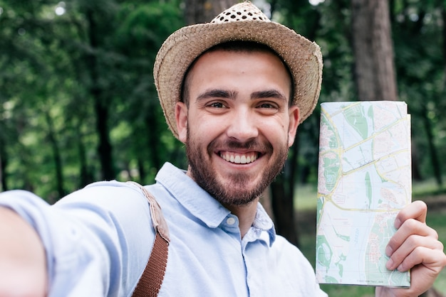 Porträt des lächelnden mannes die karte halten, die selfie an draußen nimmt
