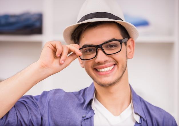 Porträt des lächelnden mannes in den gläsern und im hut