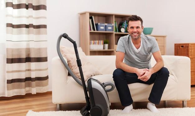 Porträt des lächelnden mannes mit staubsauger im wohnzimmer