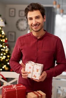 Porträt des lächelnden mannes mit weihnachtsgeschenk