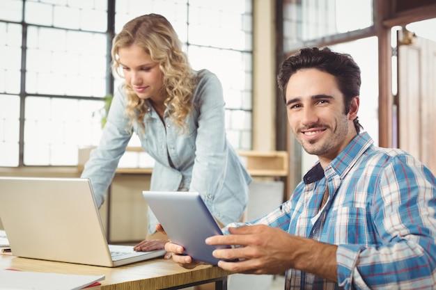 Porträt des lächelnden mannes tablette mit der frau halten, die im büro arbeitet