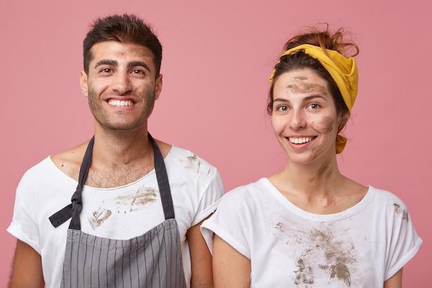 Porträt des lächelnden mannes und der lächelnden frau in den weißen t-shirts, die schmutzig sind