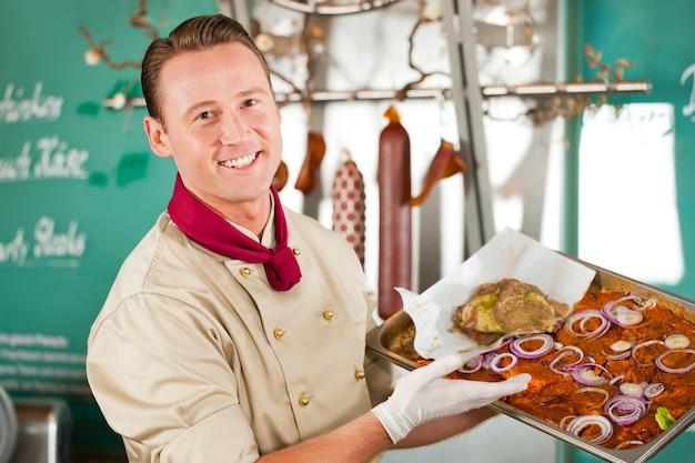 Porträt des lächelnden metzgers mit köstlichem lebensmittel geschmückt auf tellersegment