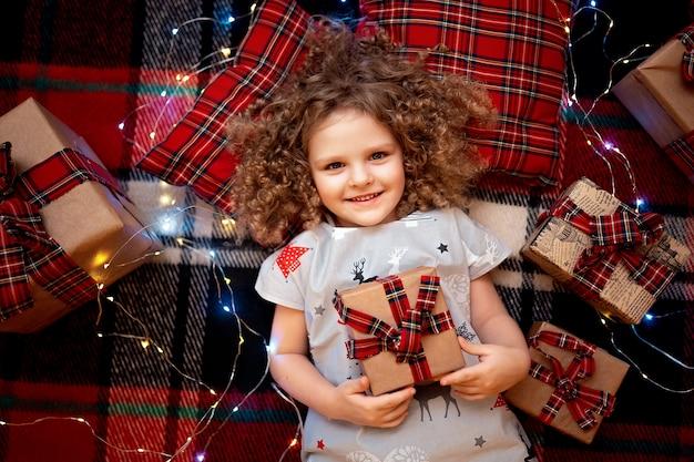 Porträt des lächelnden netten kleinen kindes in den feiertagsweihnachtspyjamas, die geschenkbox halten. ansicht von oben.