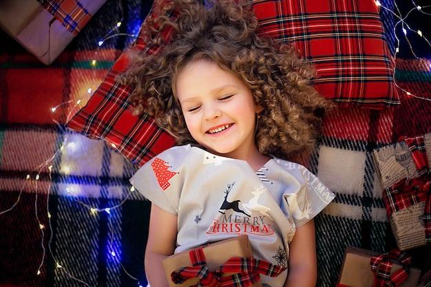 Porträt des lächelnden netten kleinen kindes in den feiertagsweihnachtspyjamas, die geschenkbox halten