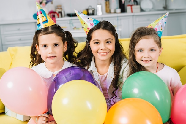 Porträt des lächelnden netten mädchens mit bunten ballonen