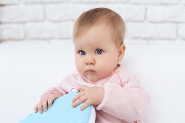 Porträt des lächelnden neugeborenen babys, das spielzeug spielt.