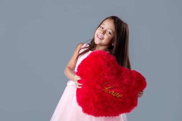 Porträt des lächelnden niedlichen kleinen mädchens im rosa kleid, das großes rotes herz hält