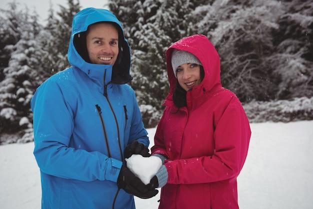 Porträt des lächelnden paares in der warmen kleidung, die schneebedecktes herz hält